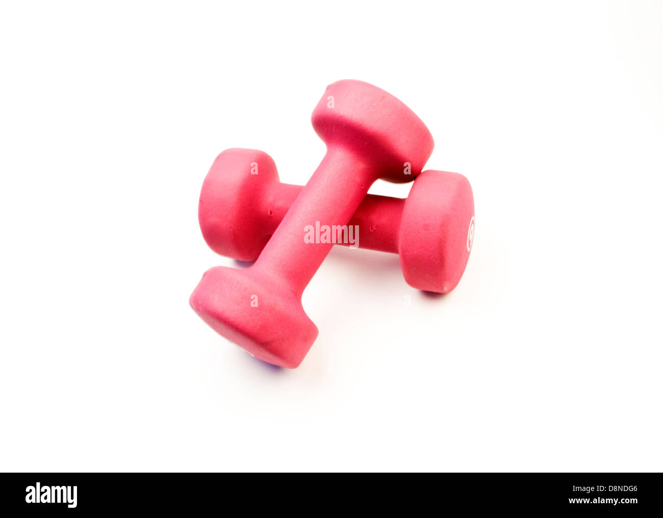 A pair of pink weights is seen against a white background - Stock Image