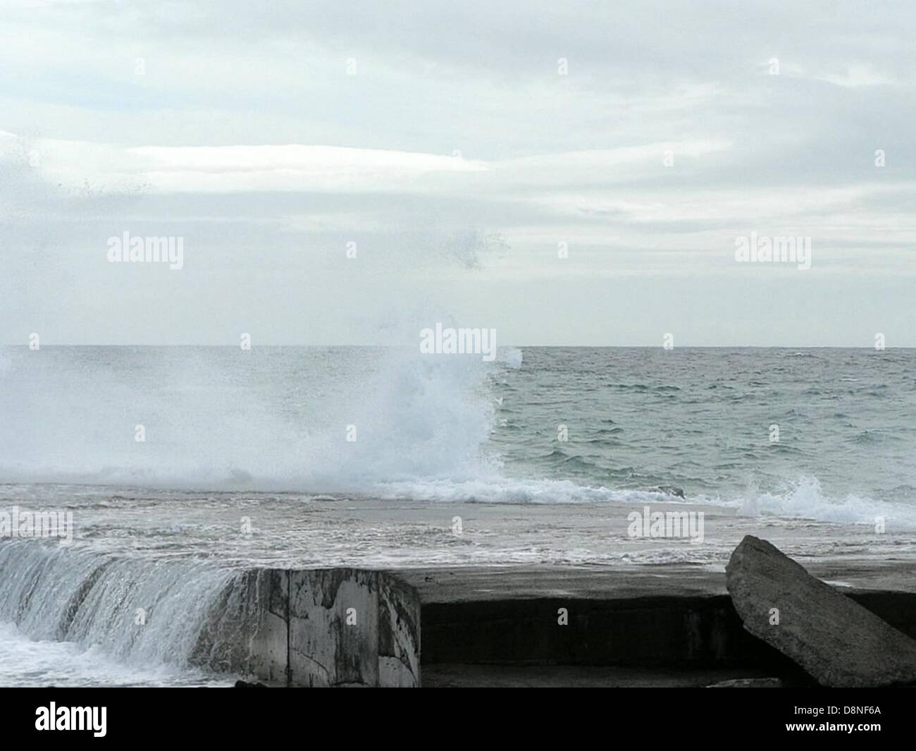 Wave breaking on rocks on the beach. - Stock Image