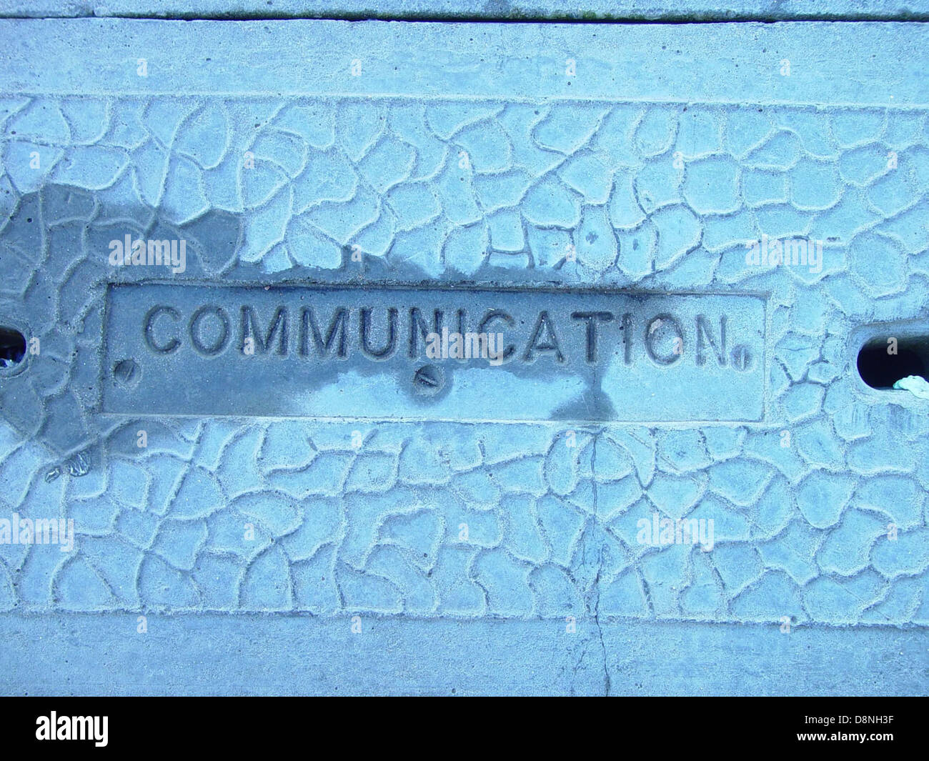 Word recessed into concete cover communication. - Stock Image