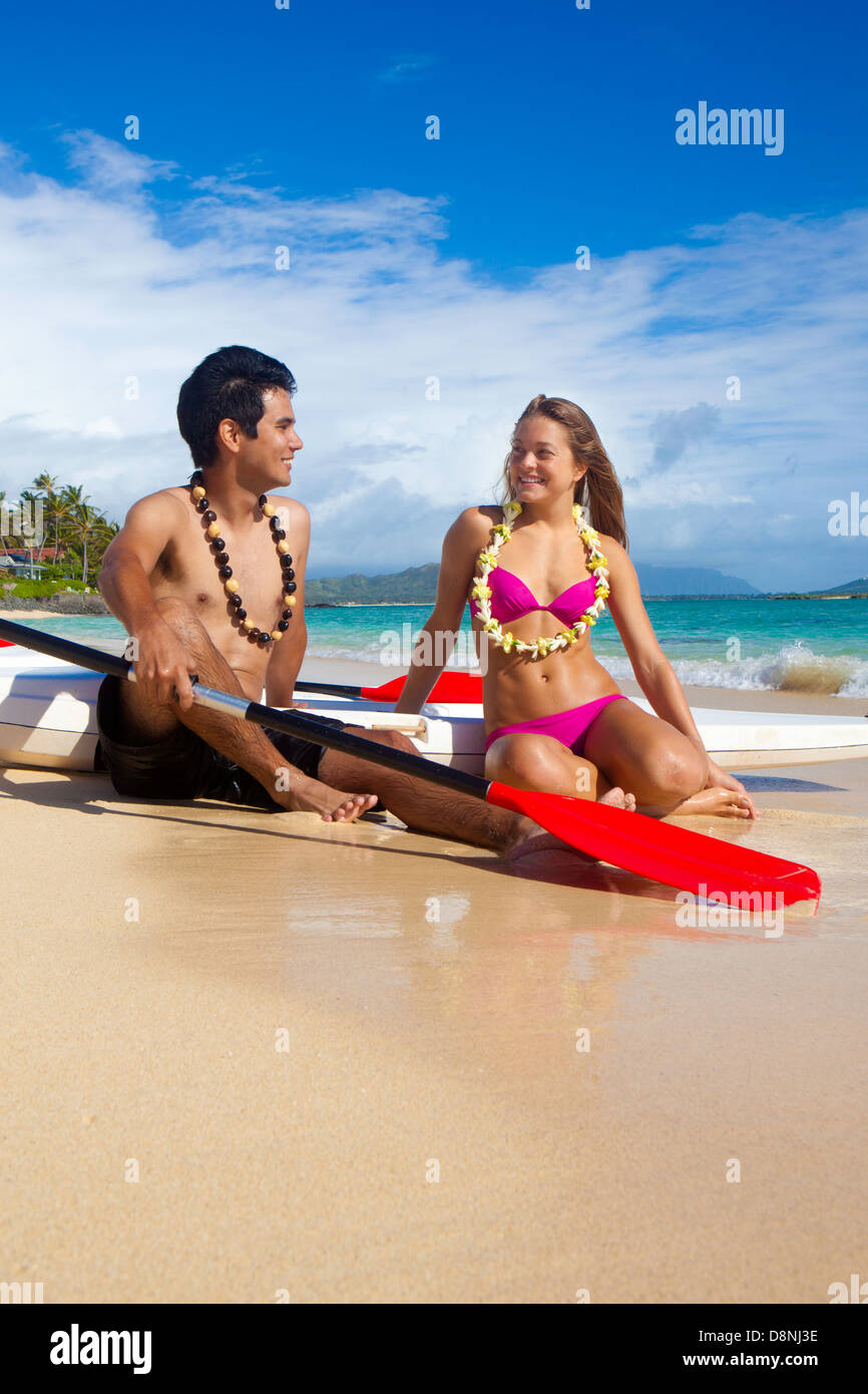 couple on the beach with their paddle boards - Stock Image