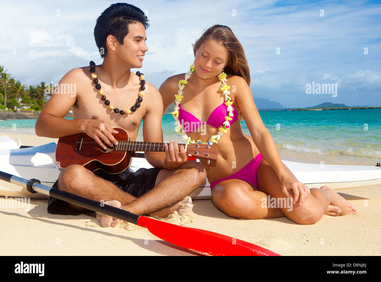 couple on the beach with their surf skis playing ukulele - Stock Image