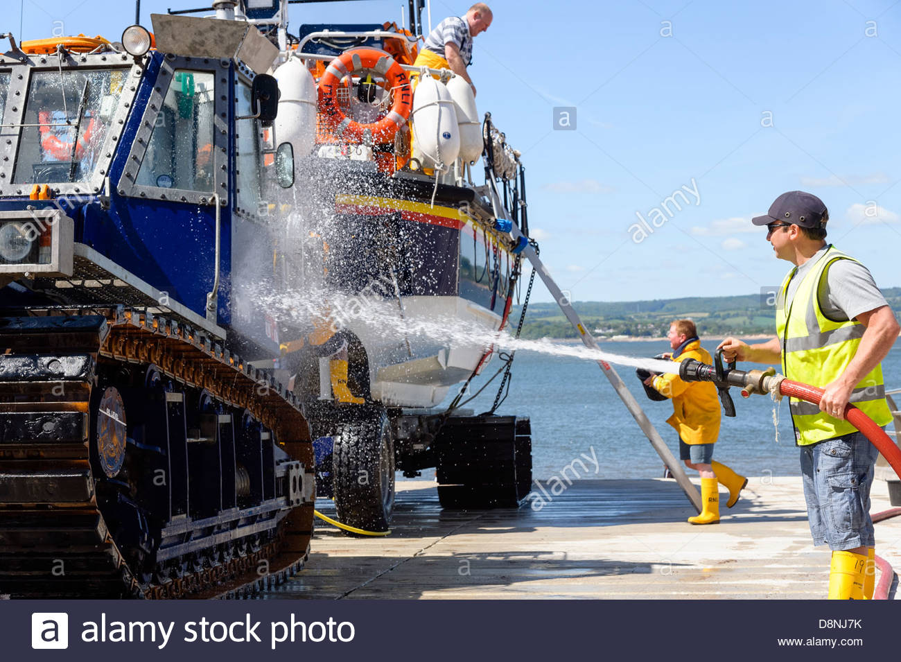 RNLI Lifeboat & tractor at Exmouth, Devon, UK. RNLI crew doing maintenance washing the lifeboat. - Stock Image
