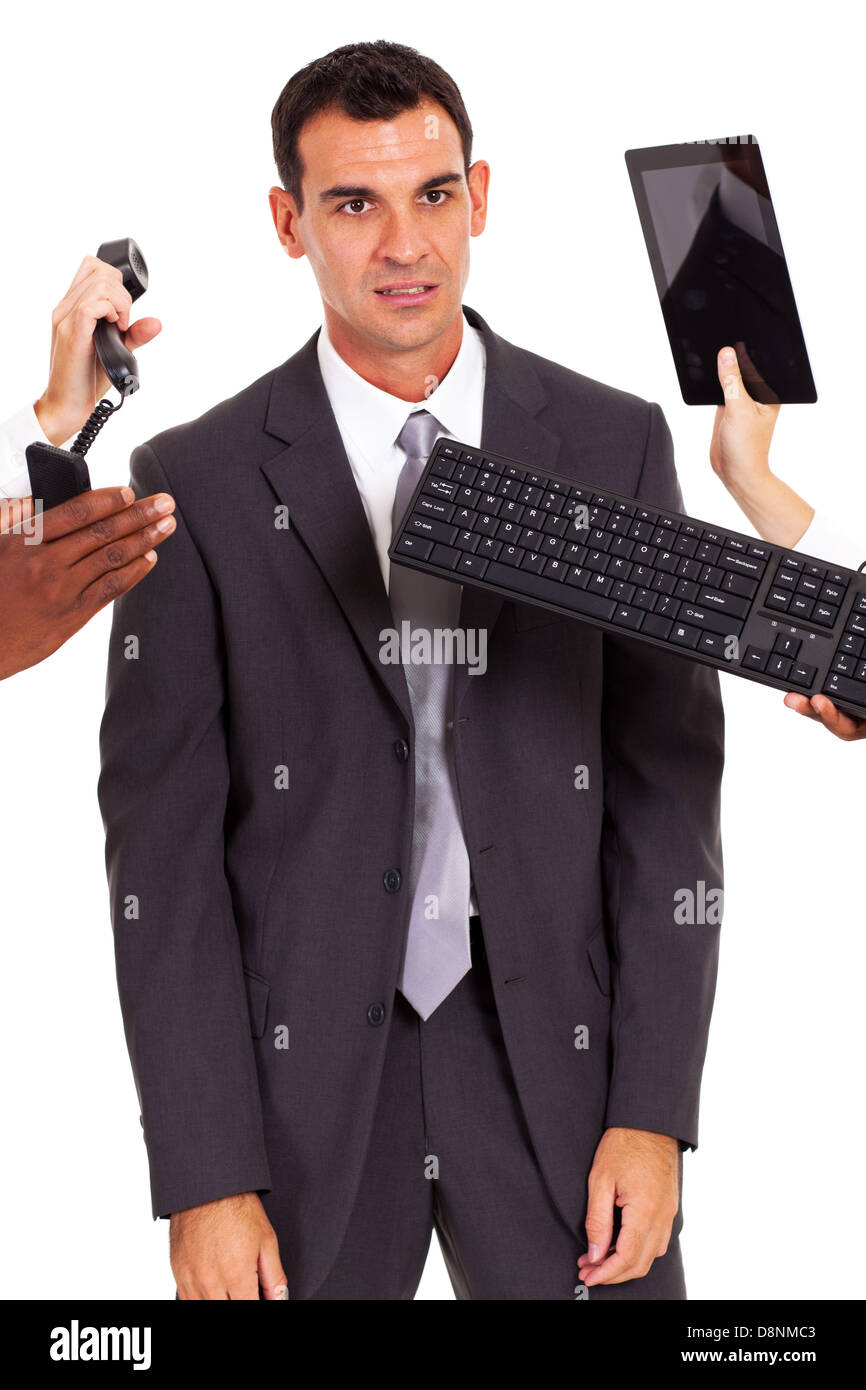 tired male office worker with multiple gadgets around him - Stock Image