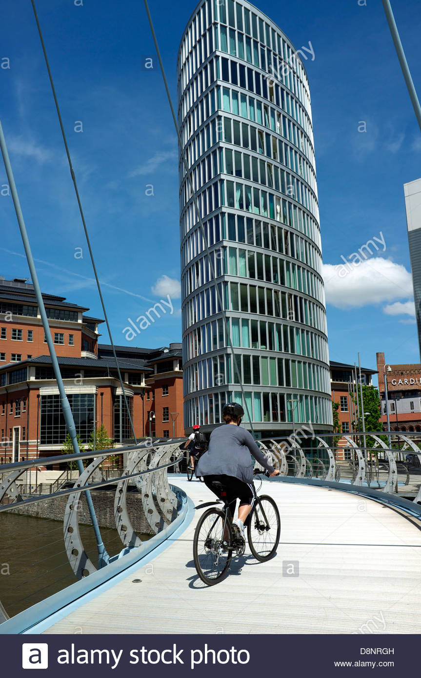 A view of the business area of Temple Quay in Bristol, UK. A cyclist passes along Valentine's Bridge. - Stock Image