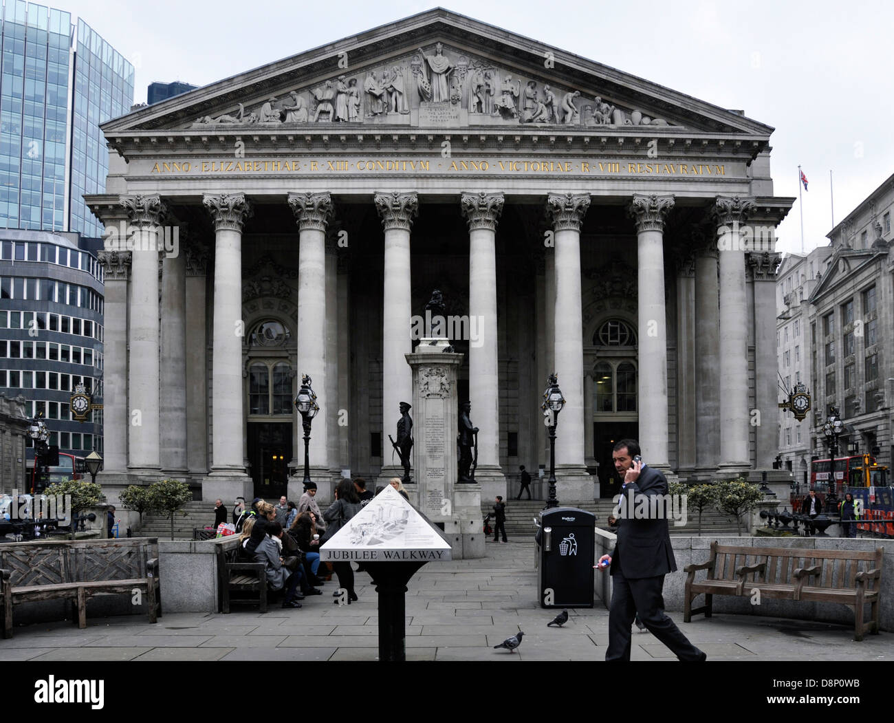 The Royal Exchange in London, with people sitting outside and a businessman passing by on his mobile phone. England, - Stock Image