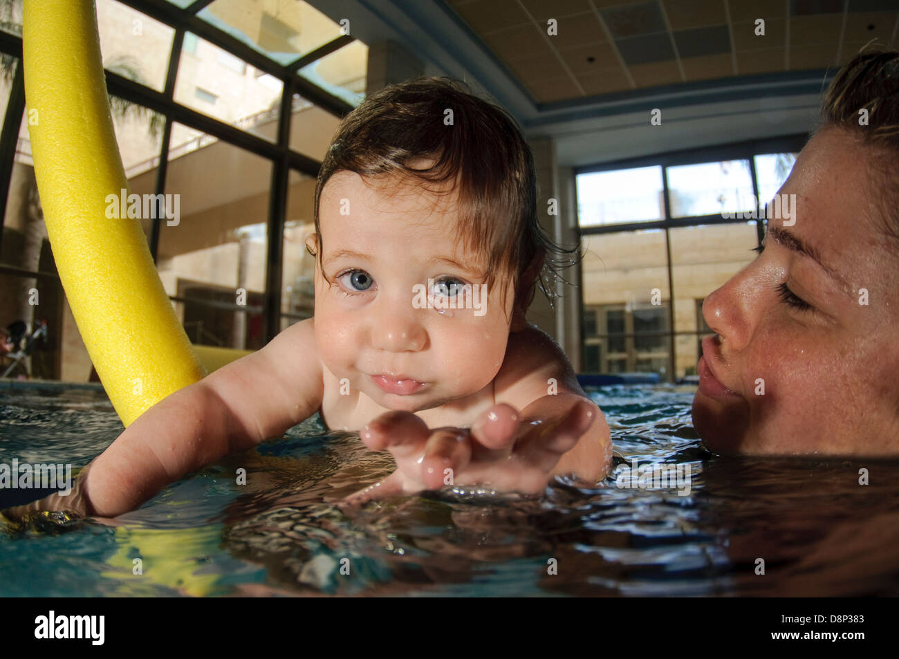 Mother with 1 year old son in a swimming pool - Stock Image