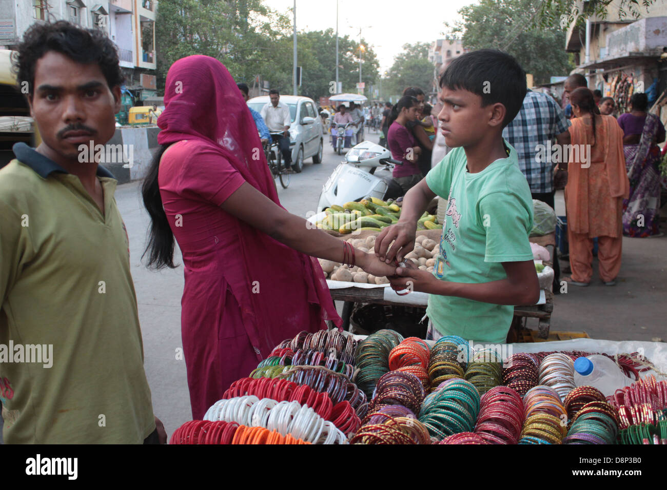 A pregnant woman tries on bangles with help from a bangle-seller in Old Delhi, India. - Stock Image
