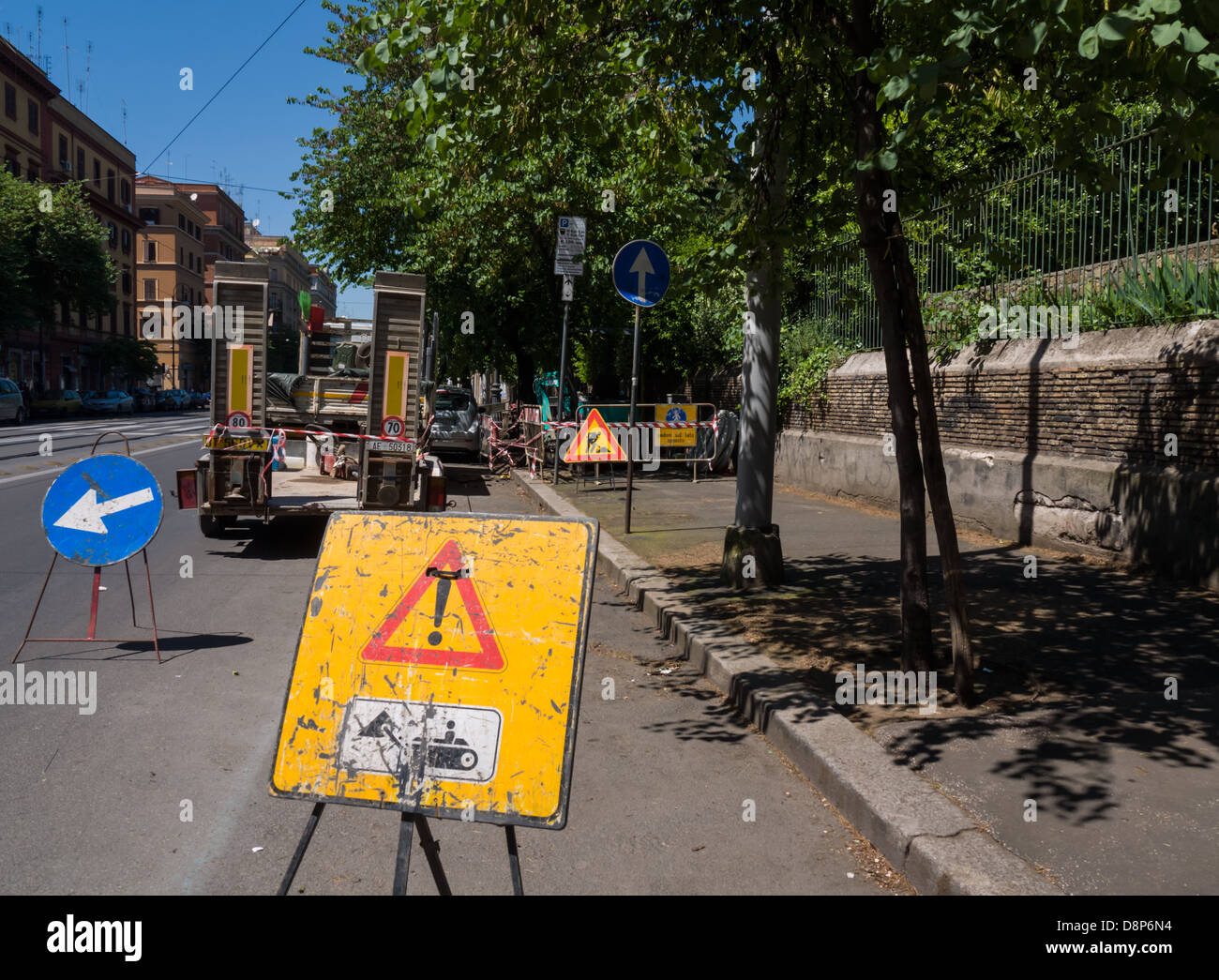 signs of a work in progress on a tree-lined street - Stock Image