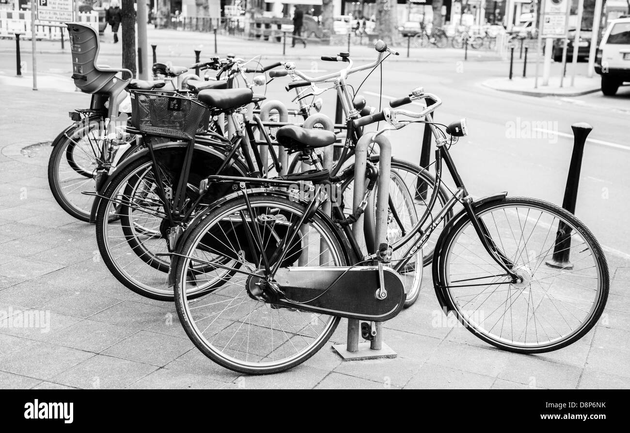 bicycles parked in a row against a lampost - Stock Image