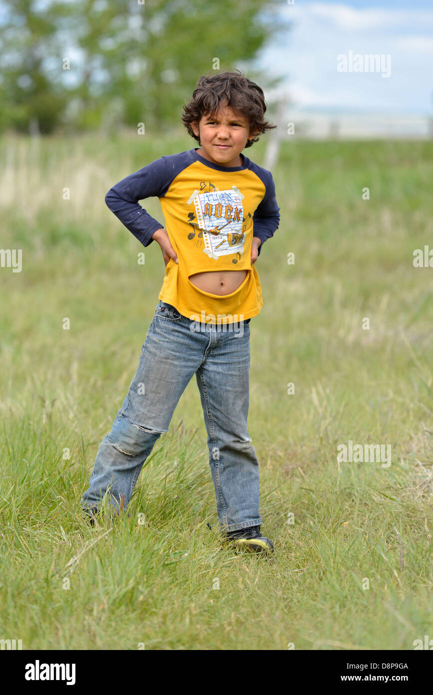 Young boy with his belly showing through a tear in his shirt, Wallowa Valley, Oregon. - Stock Image