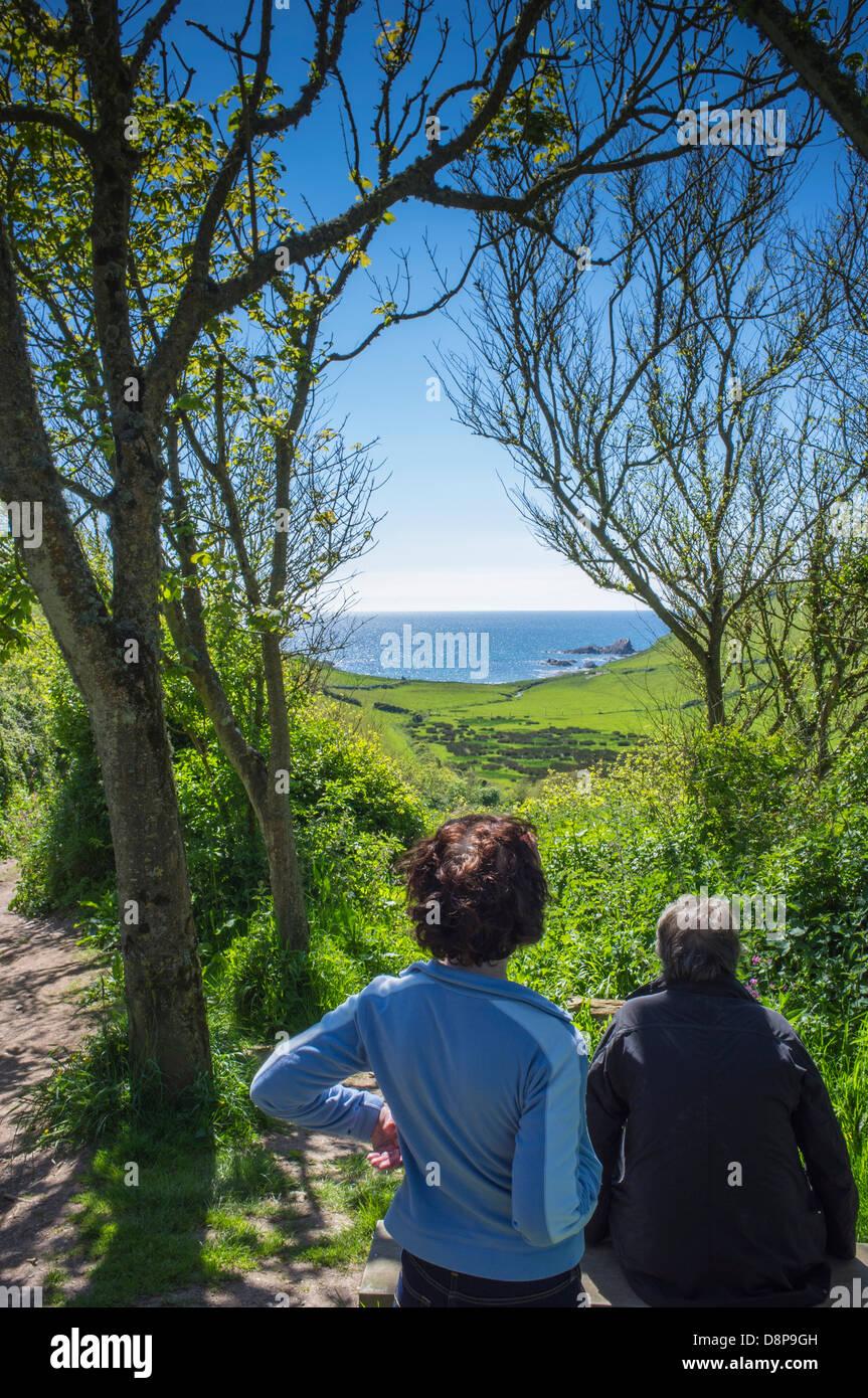 Ramblers pausing to look back at the sea. Ayrmer Cove, South Hams, Devon. UK - Stock Image