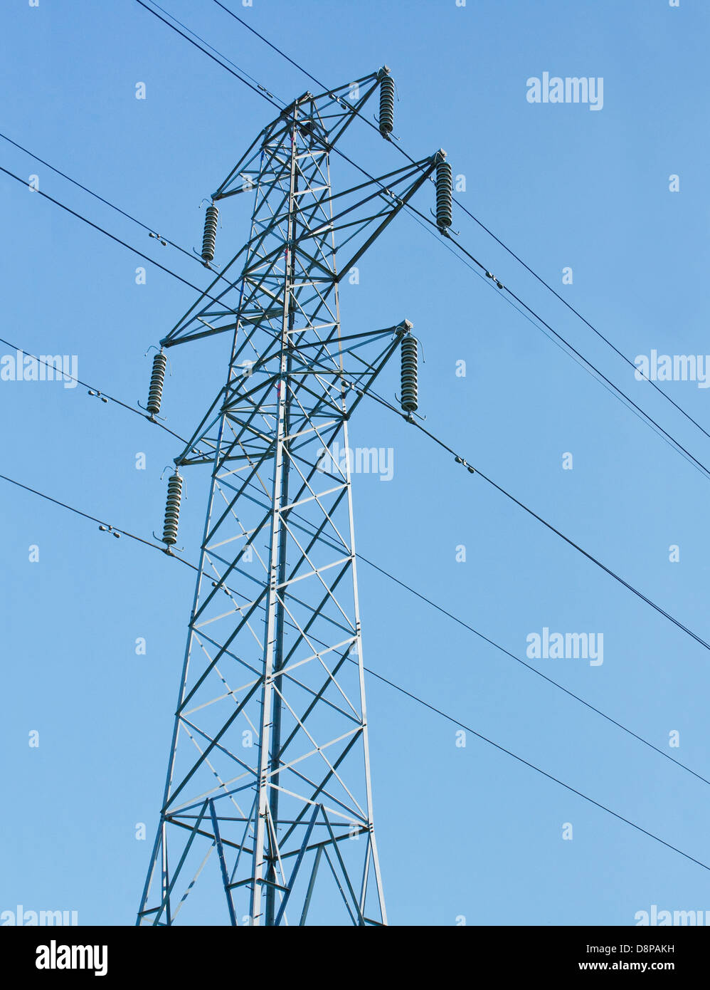 electricity pylon or transmission tower part of the national grid against a blue sky - Stock Image