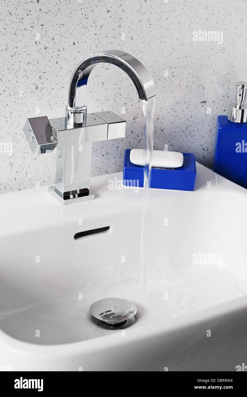 Mixer tap on a contemporary modern bathroom sink - Stock Image