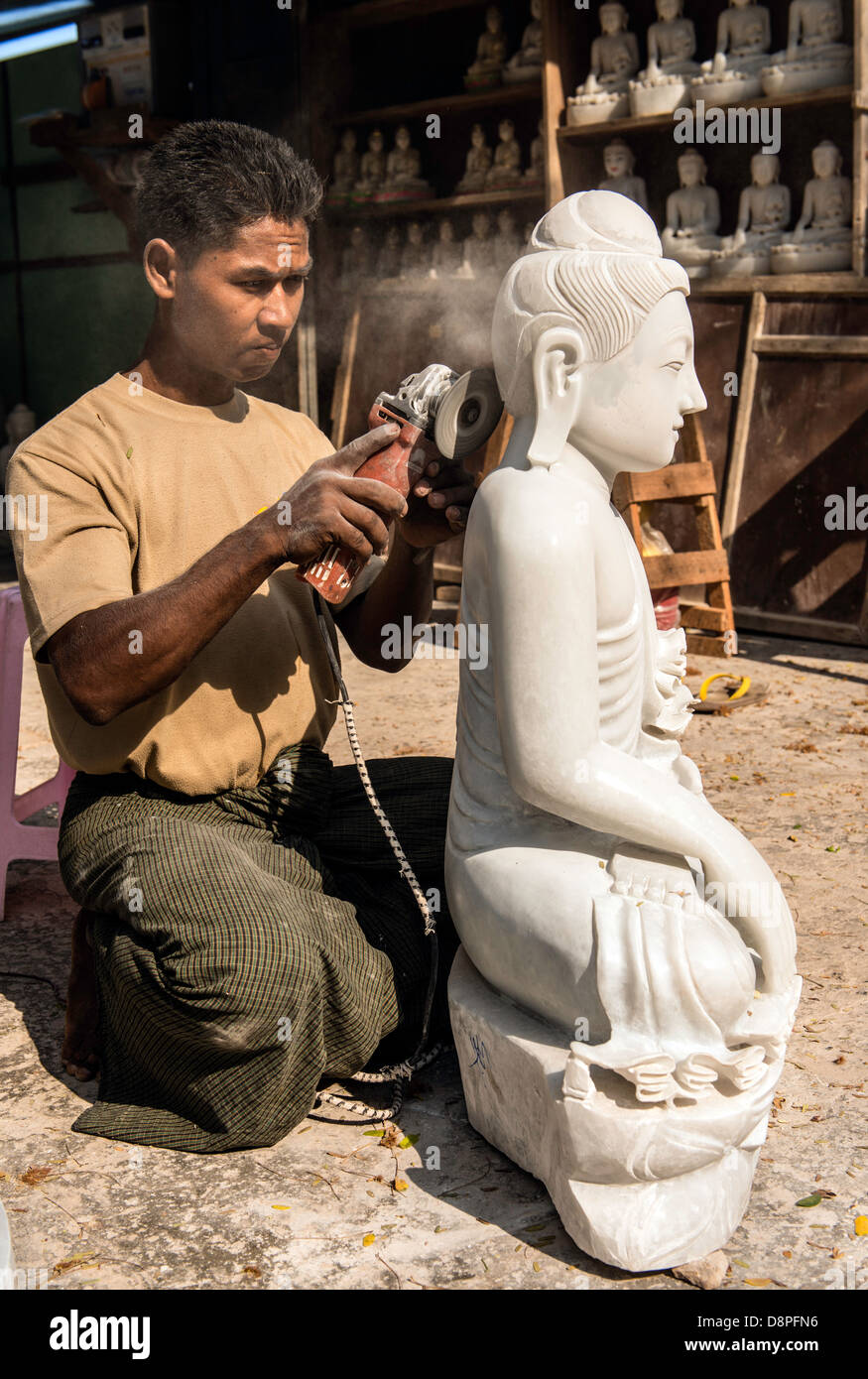 Burmese young man crafting marble effigy of Buddha statue in the marble workshop district of Mandalay Burma Myanmar Stock Photo