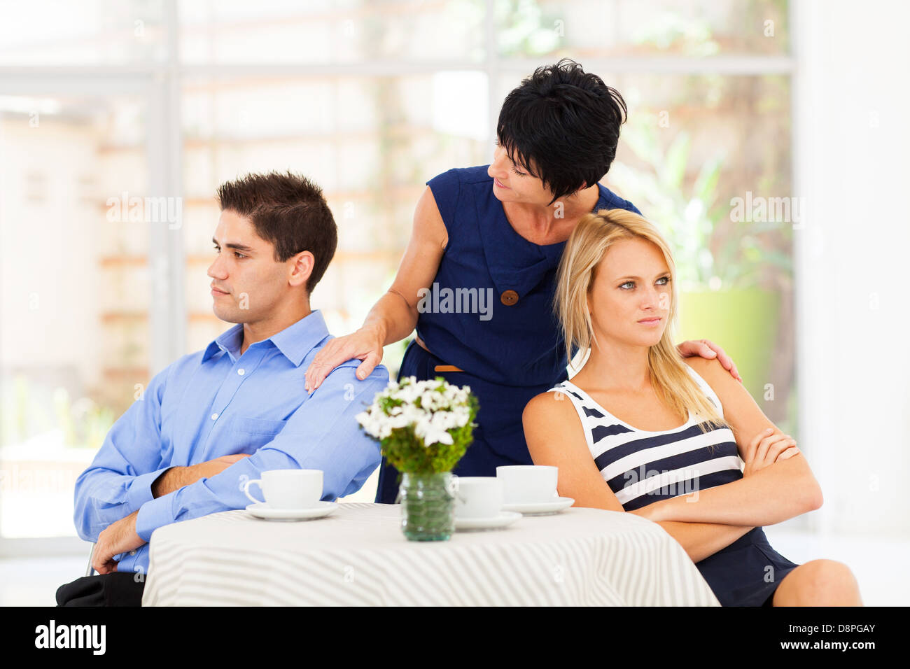 caring mother reconciling fighting young couple - Stock Image