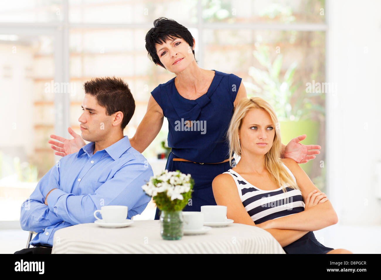 middle aged mother feeling helpless when caught in between young couple's fight - Stock Image