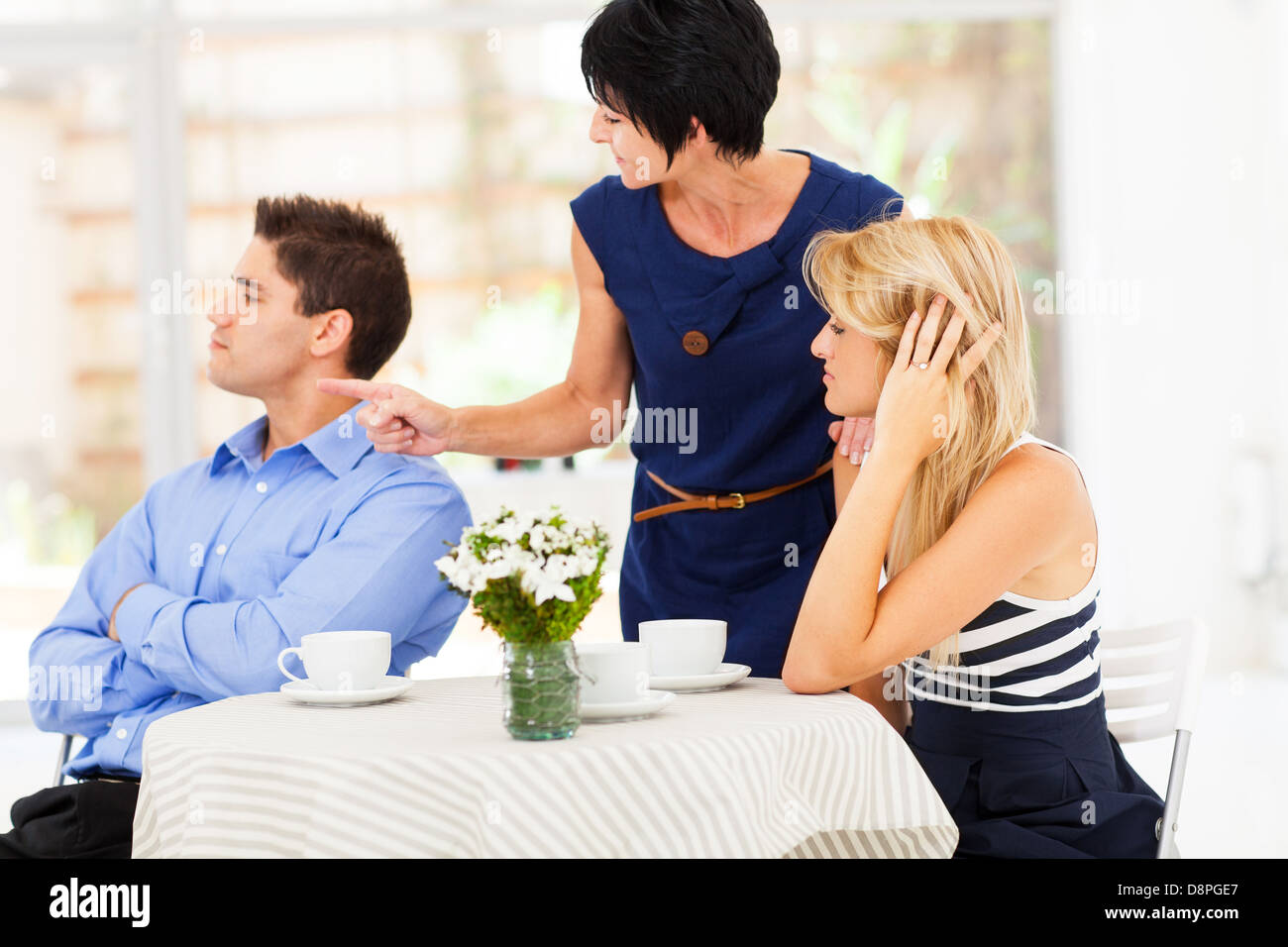 mother pointing finger at son-in-law as she took daughter's side when couple fighting - Stock Image