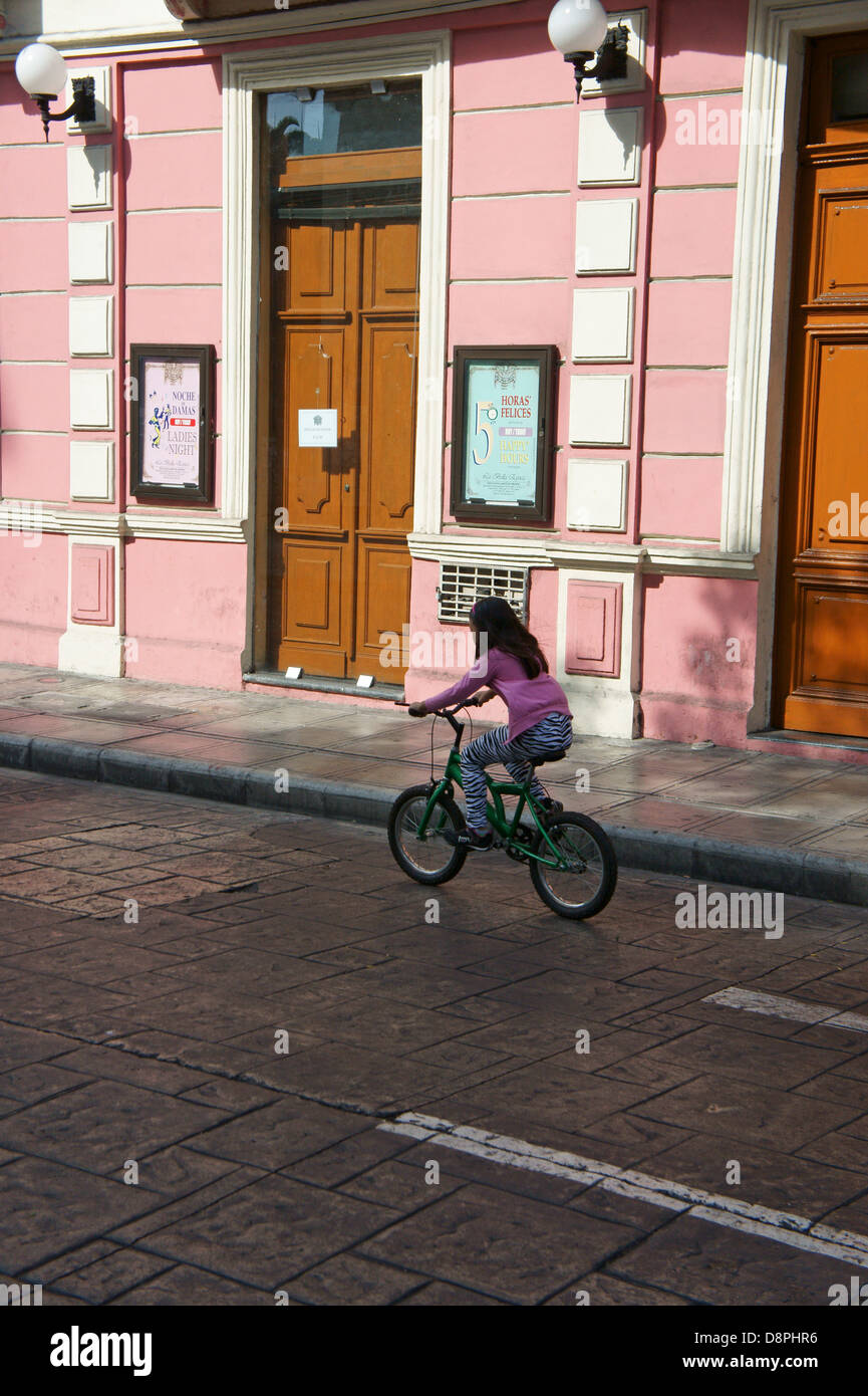 Girl riding a bicycle during Sunday bici ruta on Calle 60 in Merida, Yucatan, Mexico - Stock Image