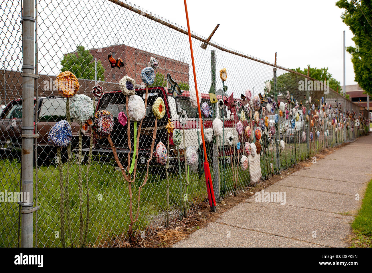 Fabric Flowers Decorating A Chain Link Fence Surrounding Junk Cars