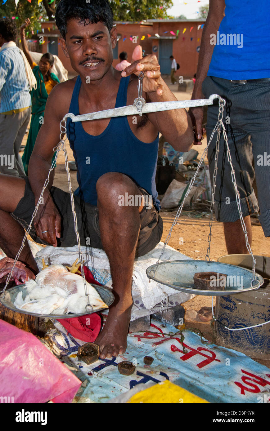 Indian vendor weighing a chicken at an open-air market in Mocha Village, Madya Pradesh, India - Stock Image