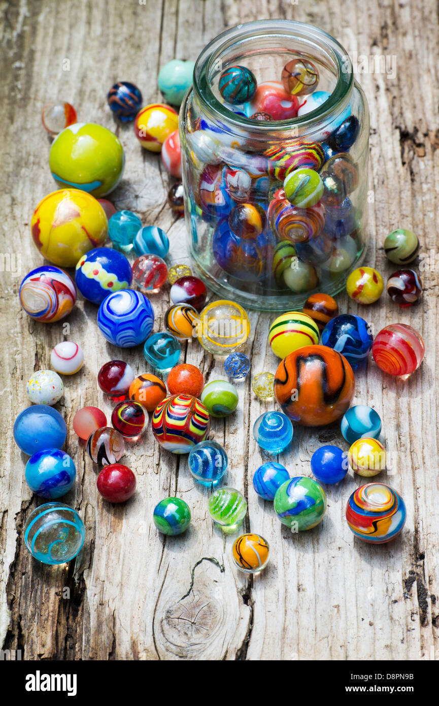 Colourful marbles and glass jar on old wood - Stock Image