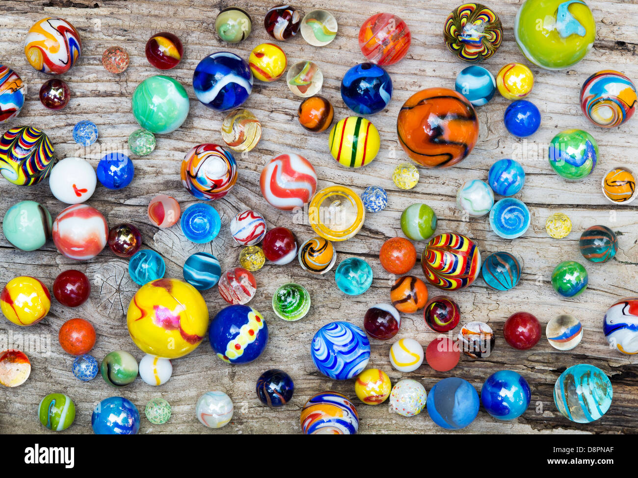Colourful marbles on old wood - Stock Image
