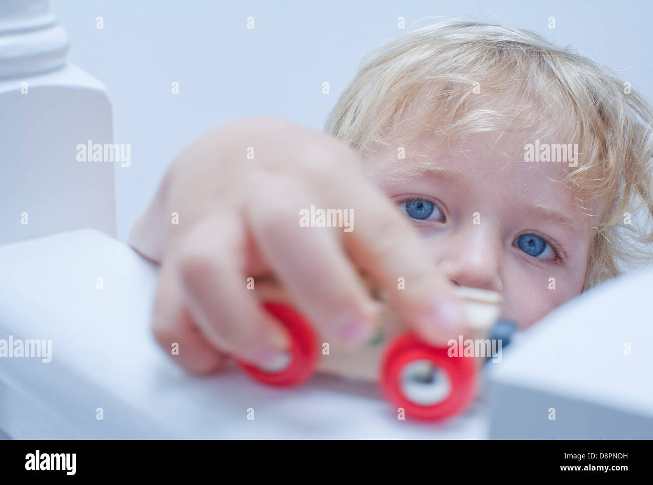 Little boy playing toy car on banister Stock Photo