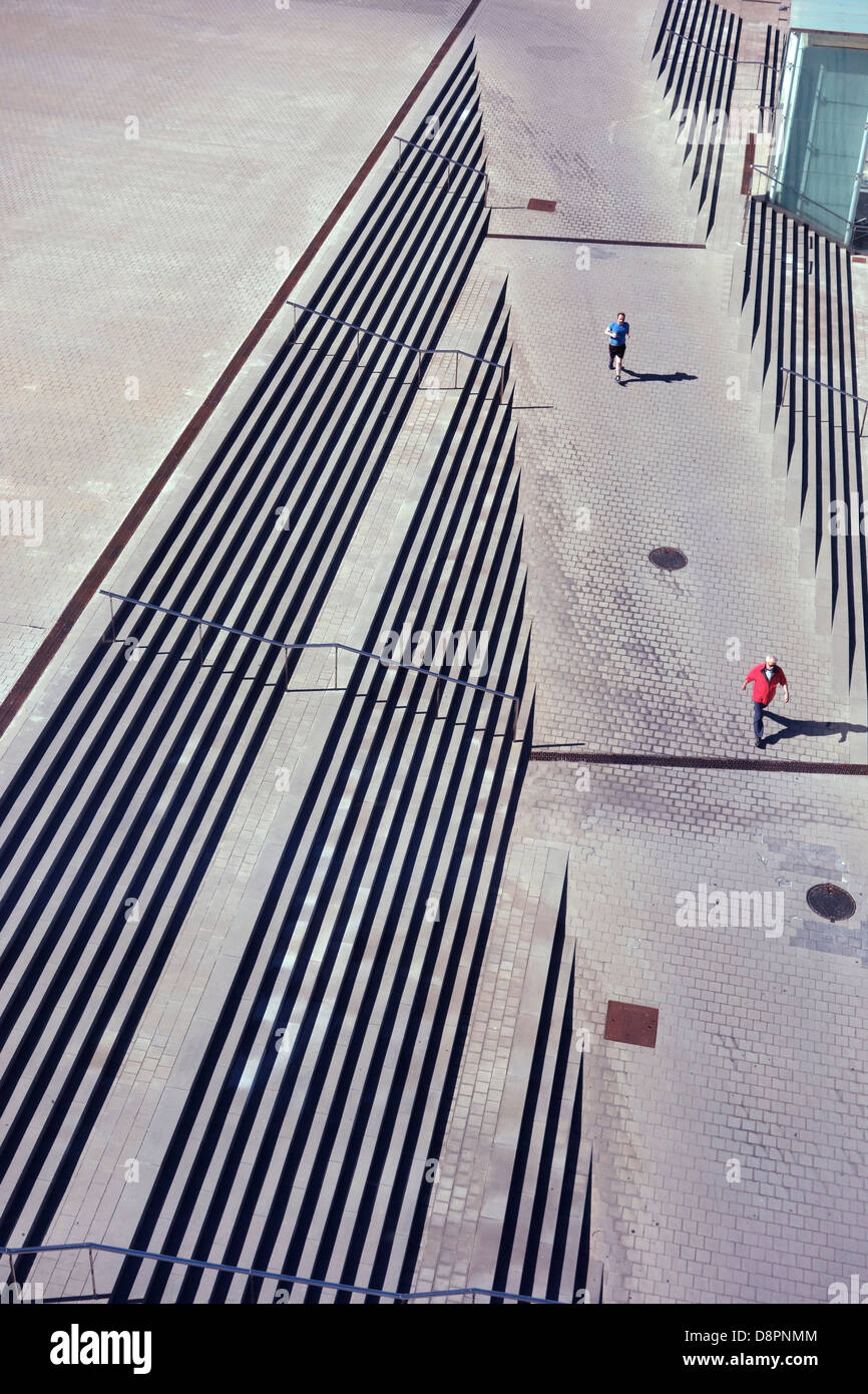Looking down to a man walking and a man  running along a path through steps creating a strange perspective - Stock Image