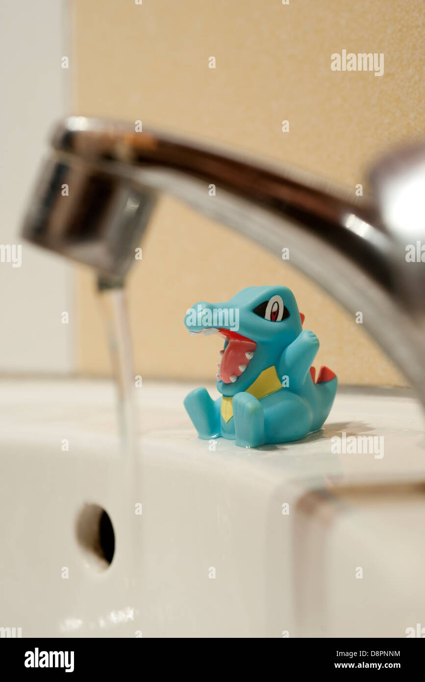Child's toy sitting on side of bathtub, water running in foreground - Stock Image