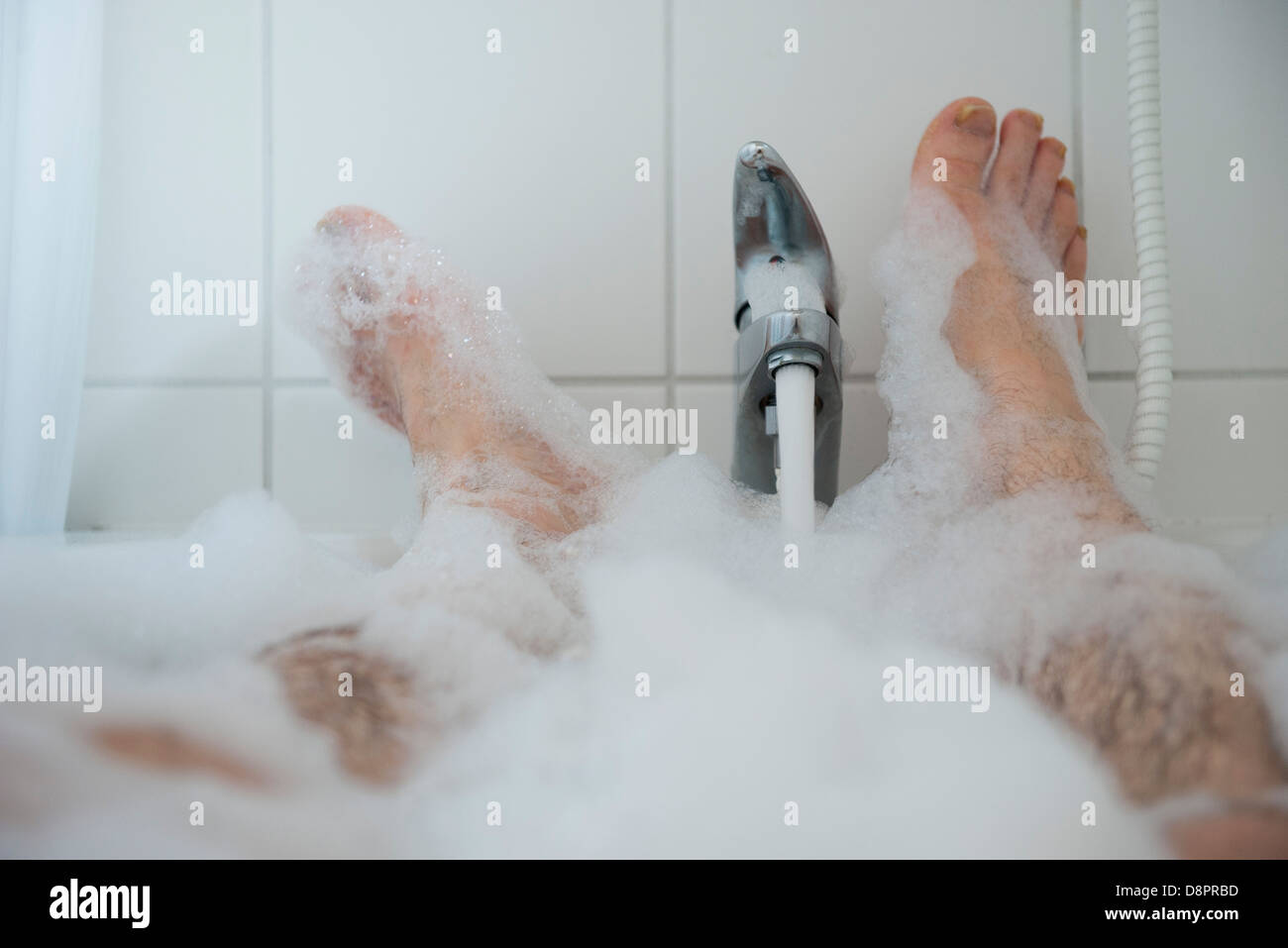 Man soaking in bubble bath, low section - Stock Image