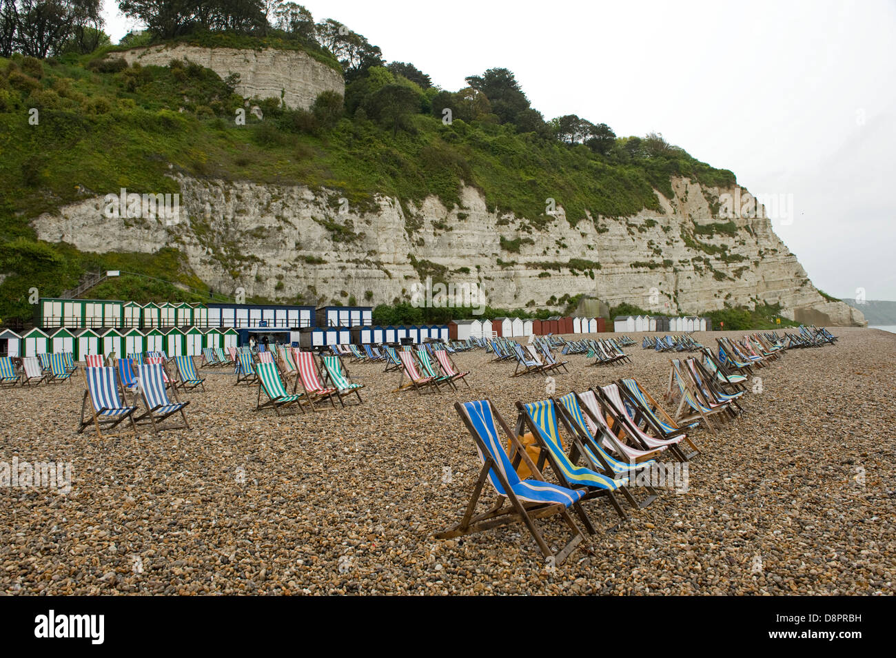 Wet summer day on Beer Beach in Devon with unused deck chairs - Stock Image