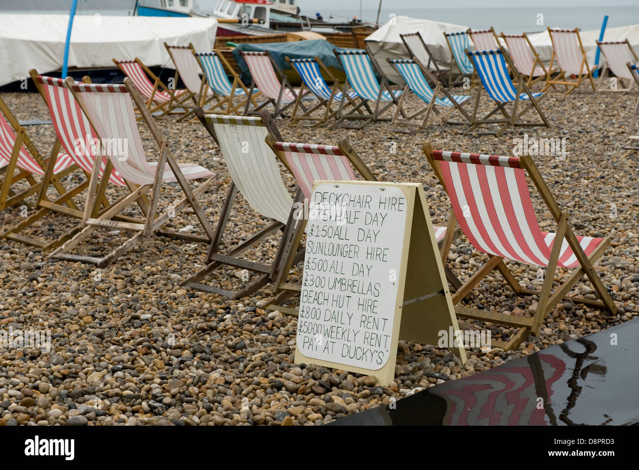 Unoccupied deck chairs and notice on a wet summer day at Beer Beach in Devon - Stock Image