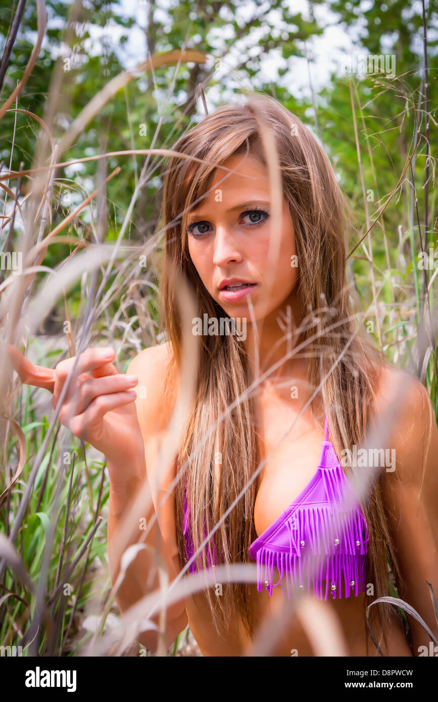 Young attractive woman in bikini, 25 years, Caucasian, standing in tall grass on the shore of the Frio River, Concan, - Stock Image