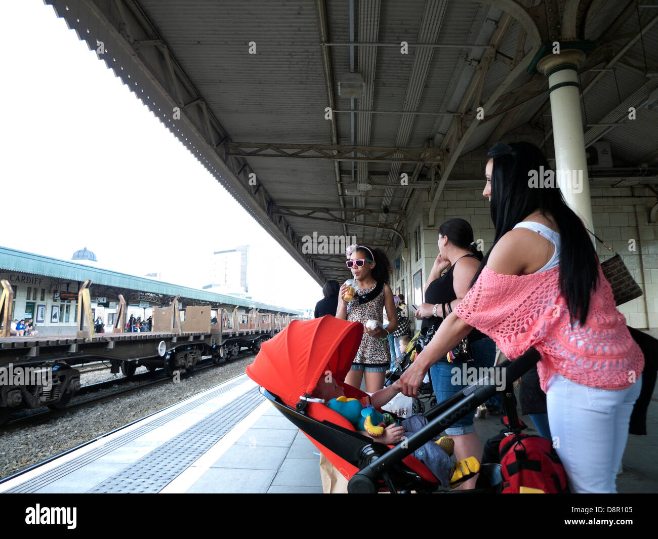 Family waiting for train on railway station platform Cardiff Central Station in Wales UK   KATHY DEWITT - Stock Image