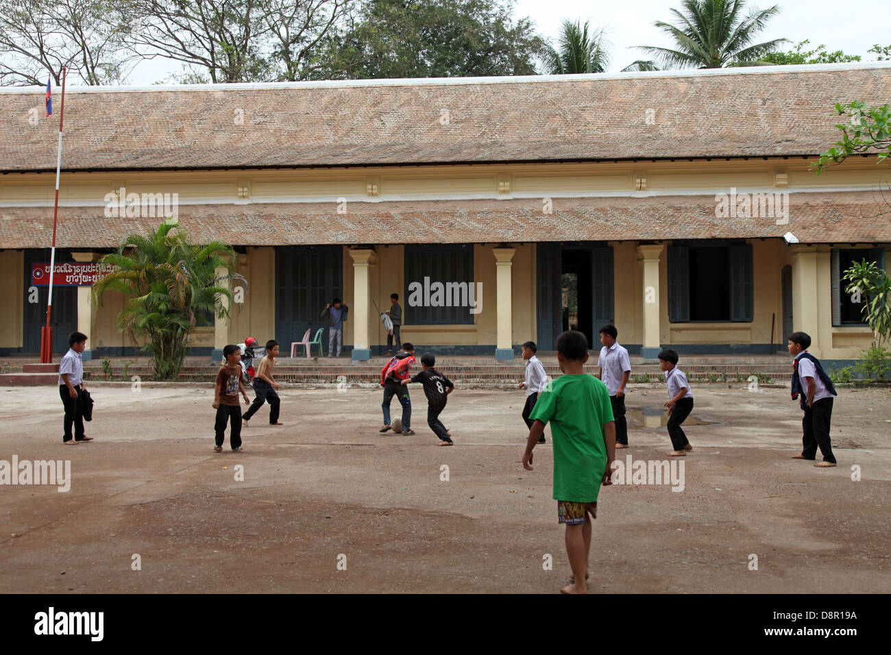 School children playing football at school ground, Luang Prabang, Laos - Stock Image