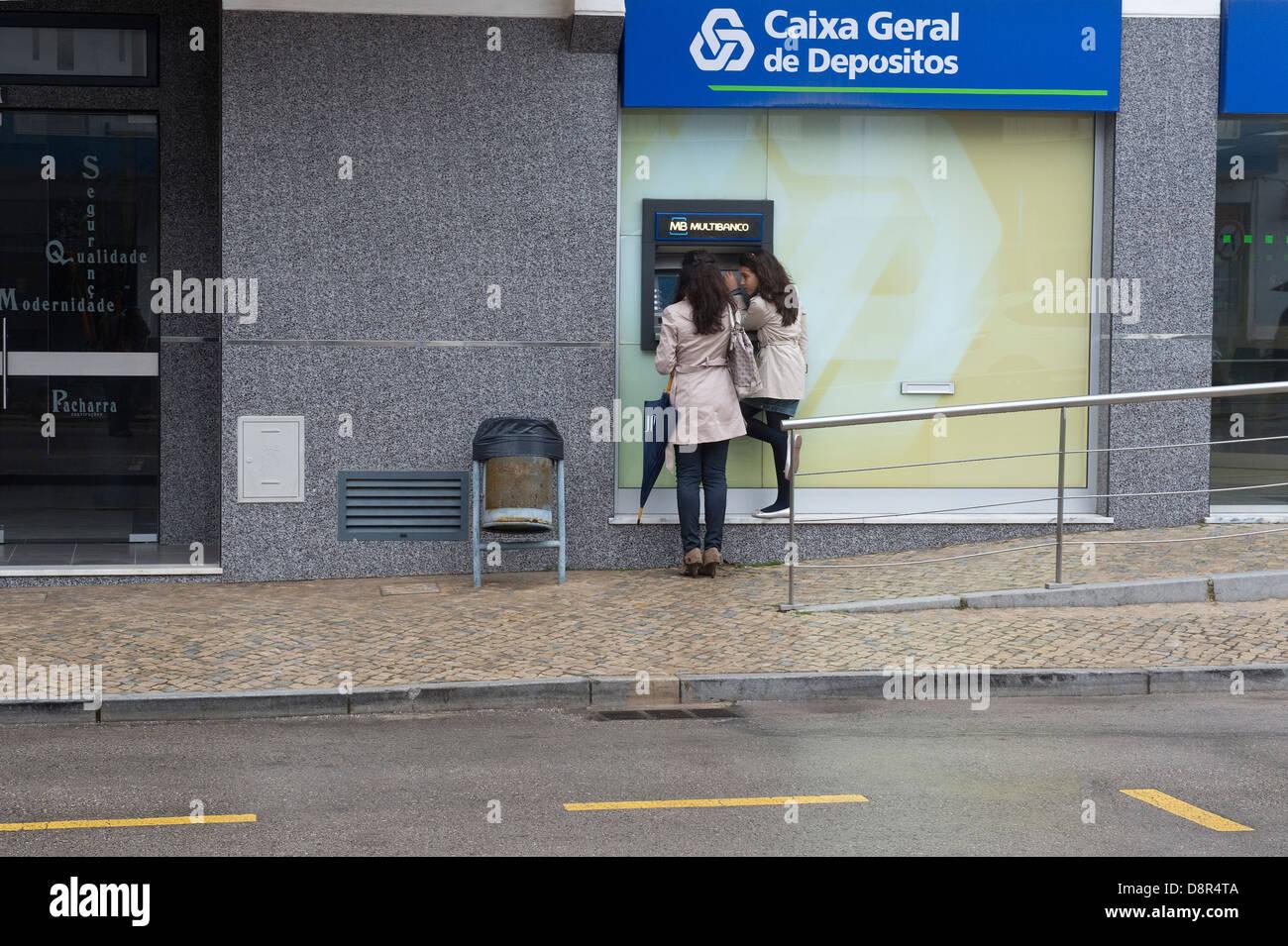 Two young woman at the Caixa Geral de Depositos cash dispensing machine São Brás de Alportel Algarve Portugal - Stock Image
