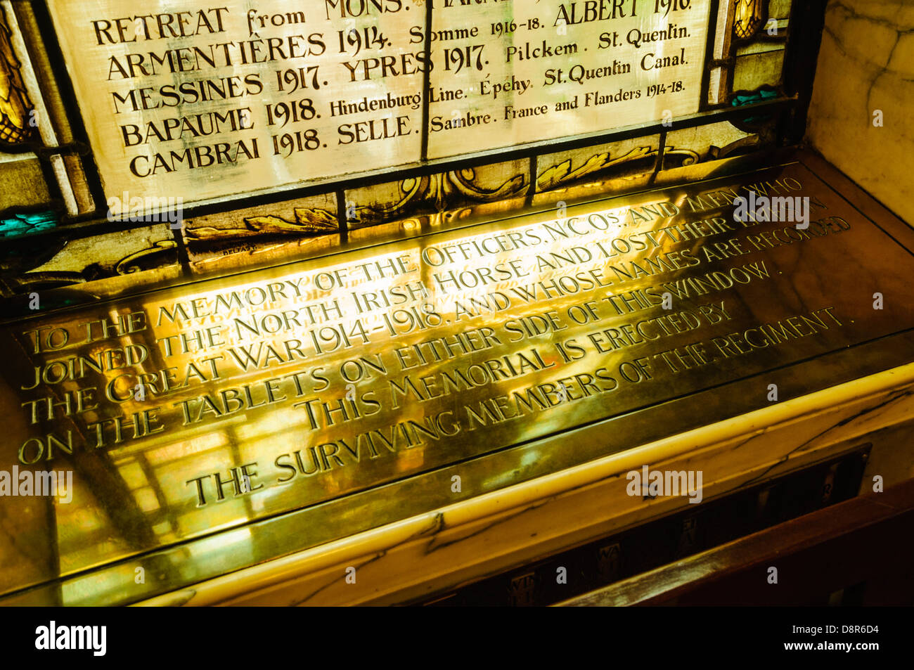 Brass plaque below a stained glass window commemorating soldiers from WW1 in Belfast City Hall. - Stock Image