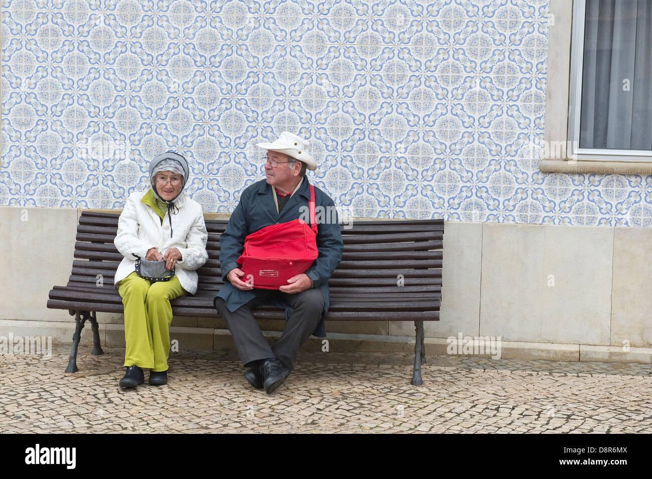 Older couple resting on the bench after Easter Sunday Flower Torches Festival São Brás de Alportel Algarve - Stock Image