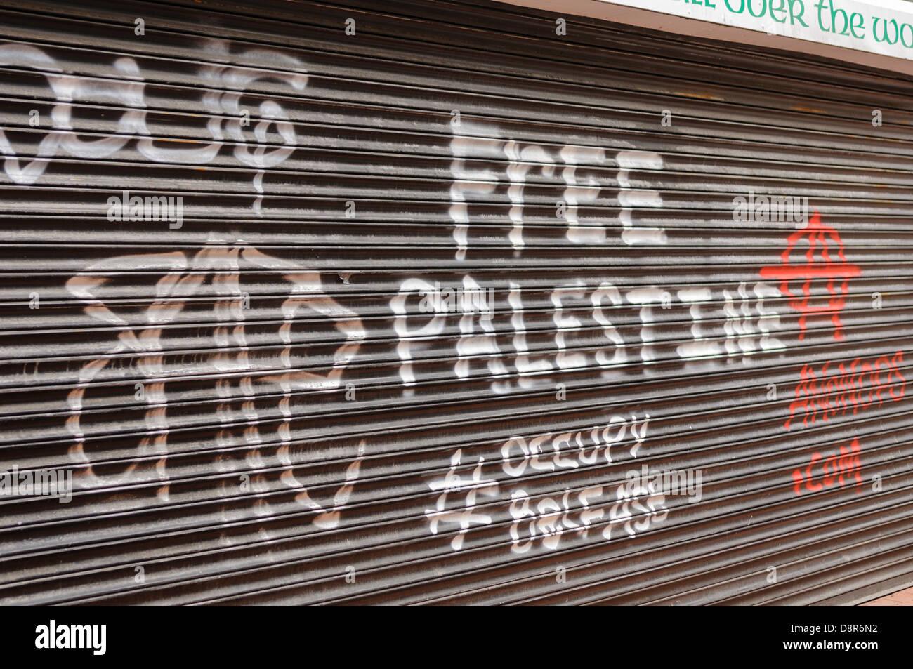 Grafitti on a shop shutter 'Free Palestine #occupy belfast' - Stock Image