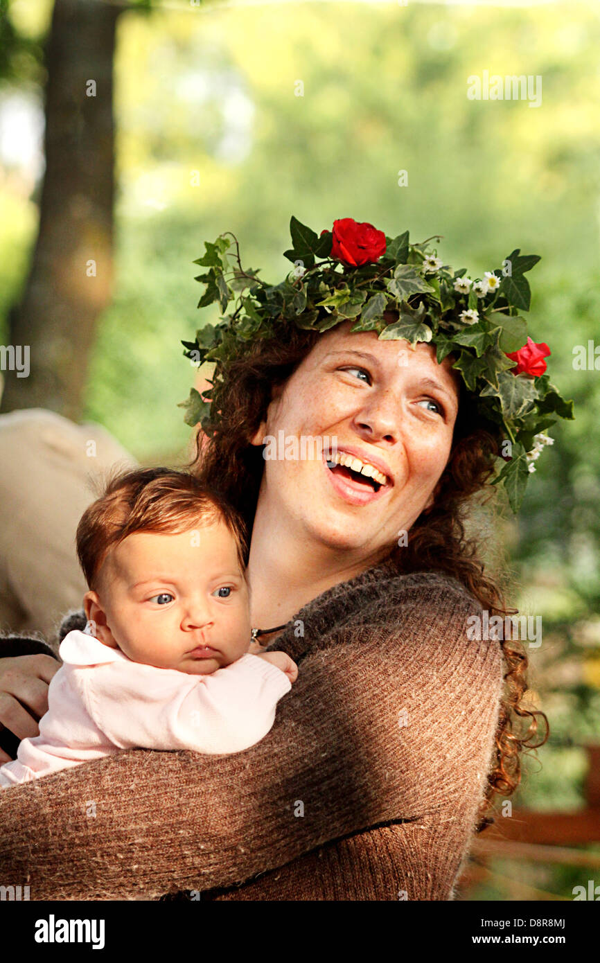 Laughing woman with a serious baby. Woman is wearing a flower wreath / at medieval fair in Provins town, France - Stock Image