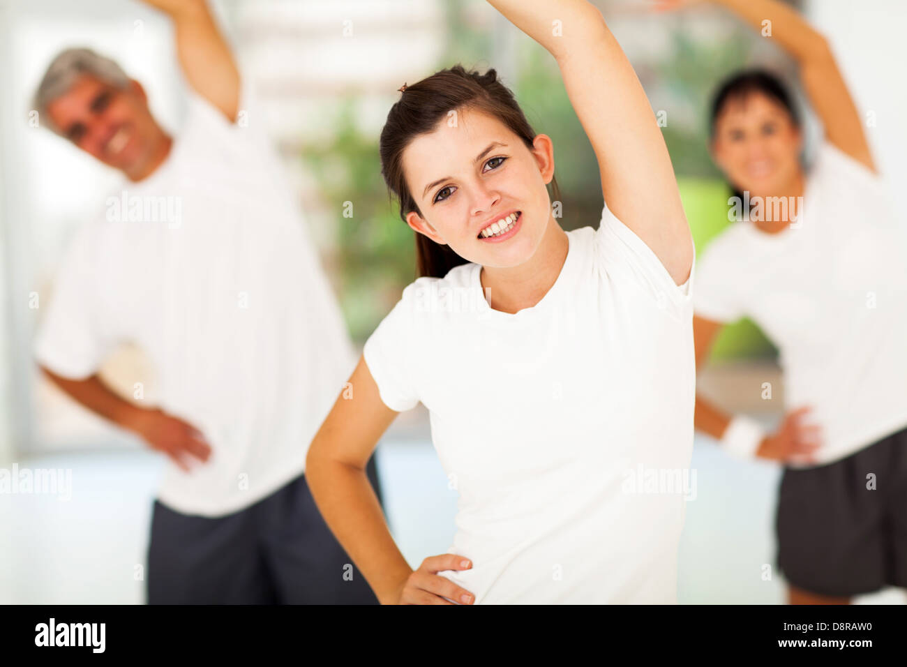beautiful young teen girl working out with parents at home - Stock Image