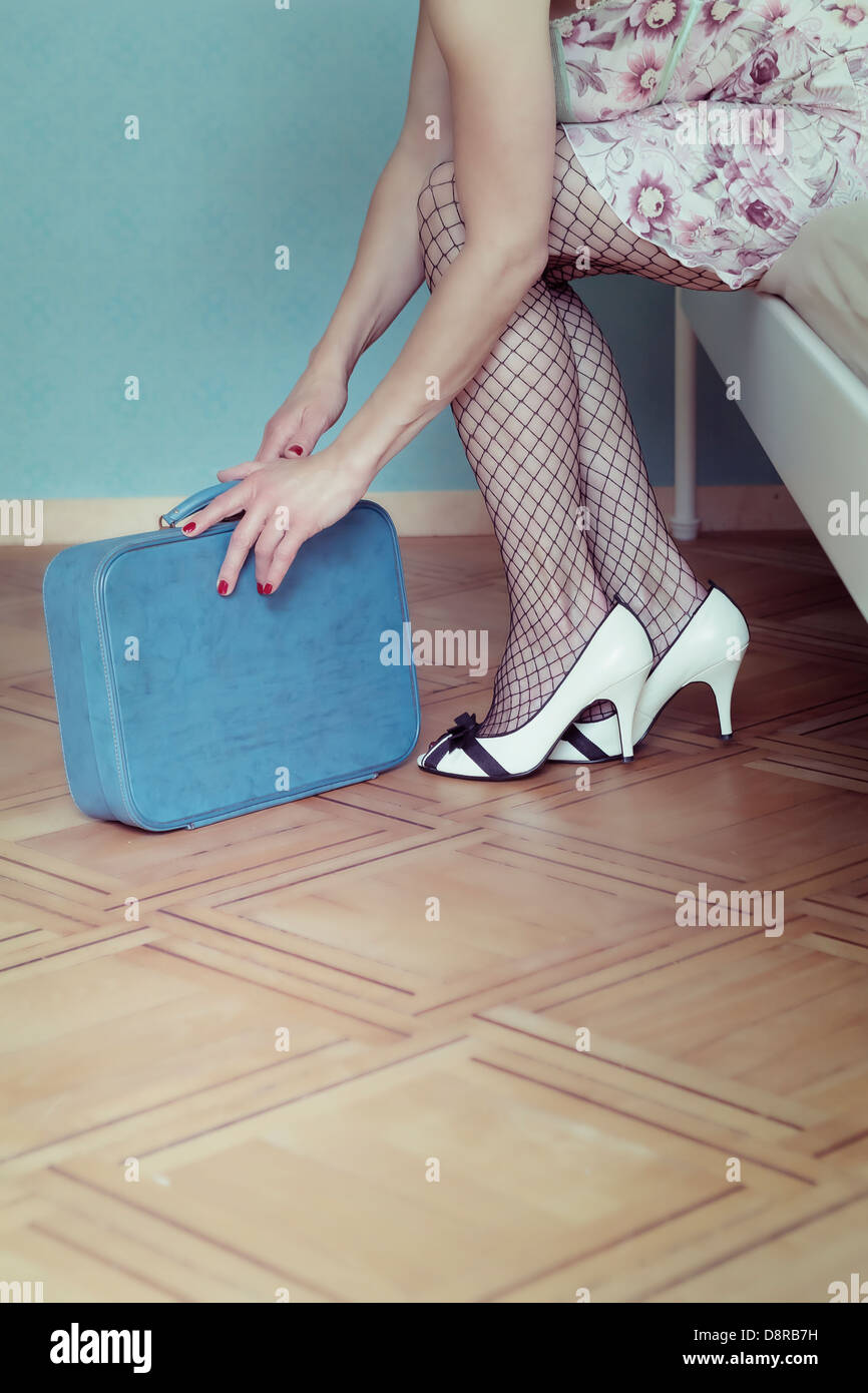 a woman in a negligee is sitting on a bed with a suitcase Stock Photo
