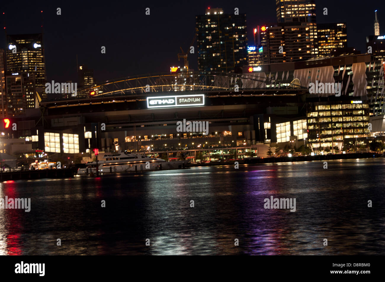 Etihad Stadium Melbourne docklands on the harbour dock waters at night - Stock Image