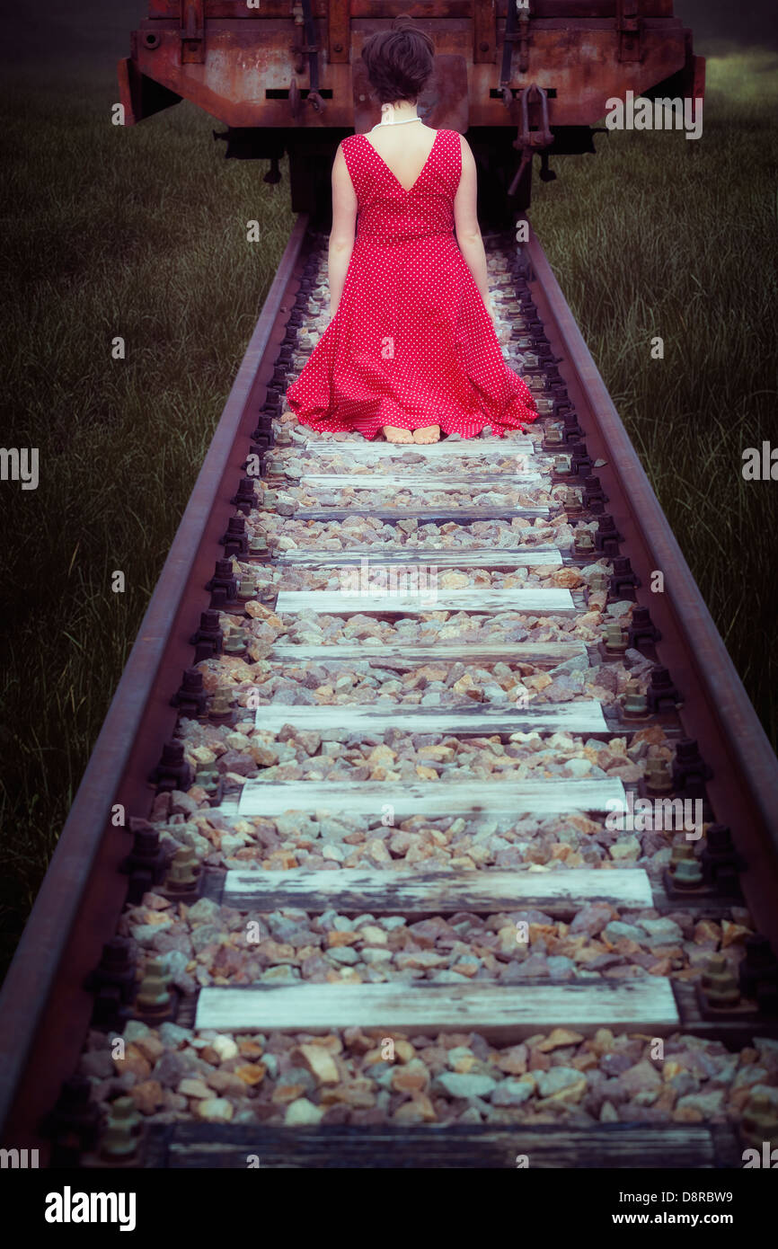 a girl in a red dress is sitting on railway tracks in front of a waggon - Stock Image