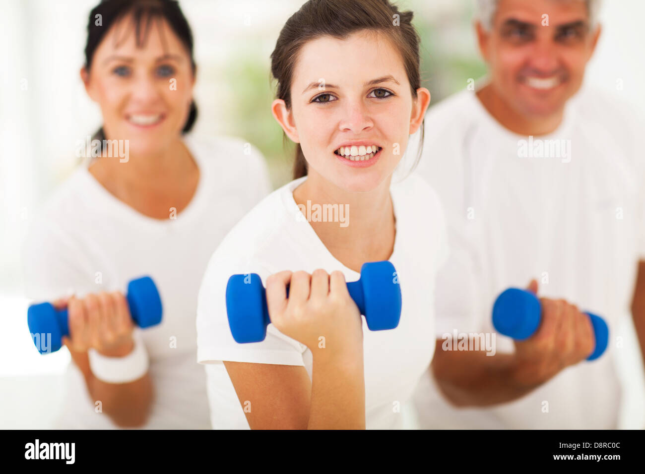 pretty teen girl working out using dumbbell with parents - Stock Image