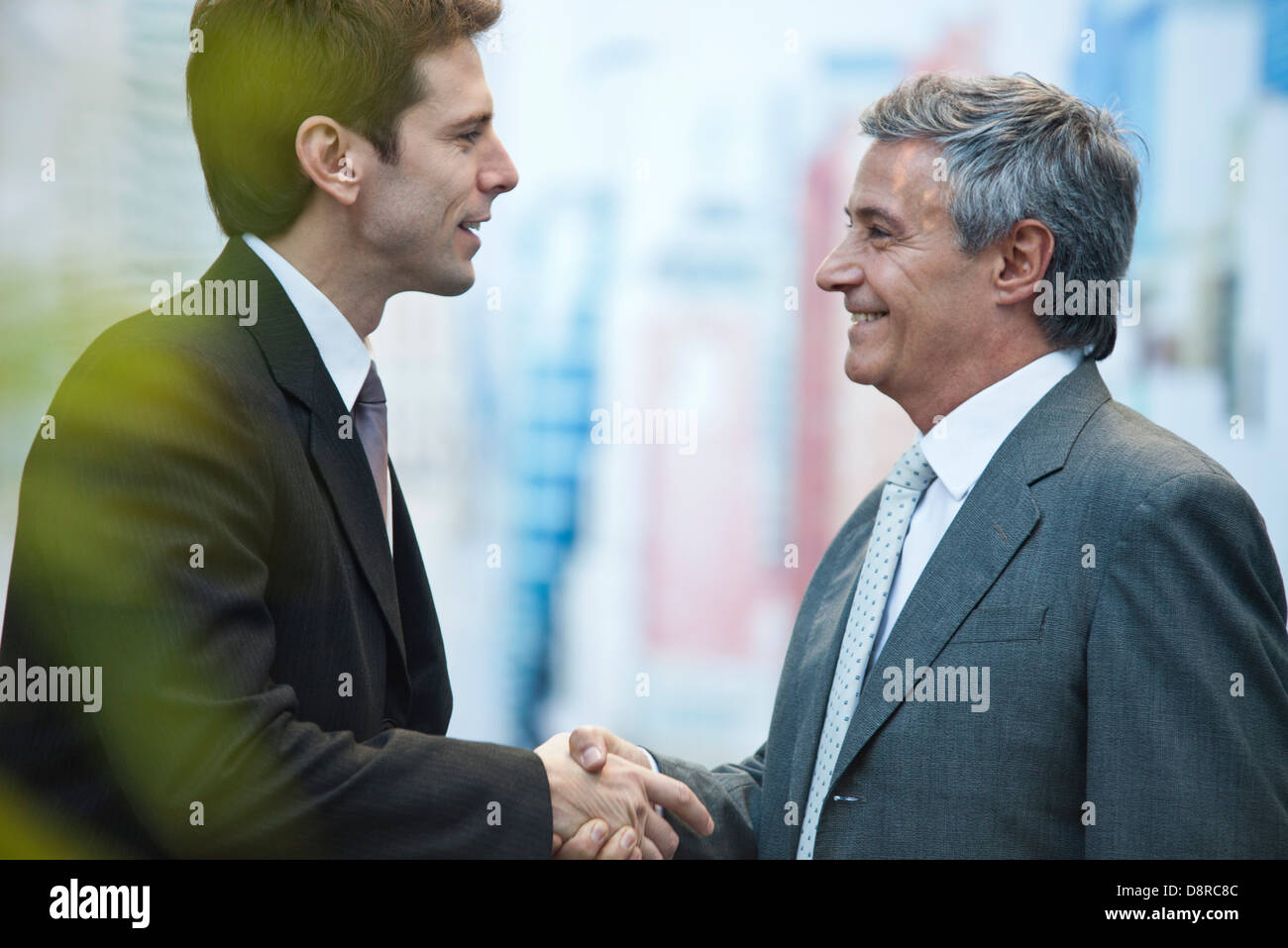 Businessmen shaking hands outdoors - Stock Image