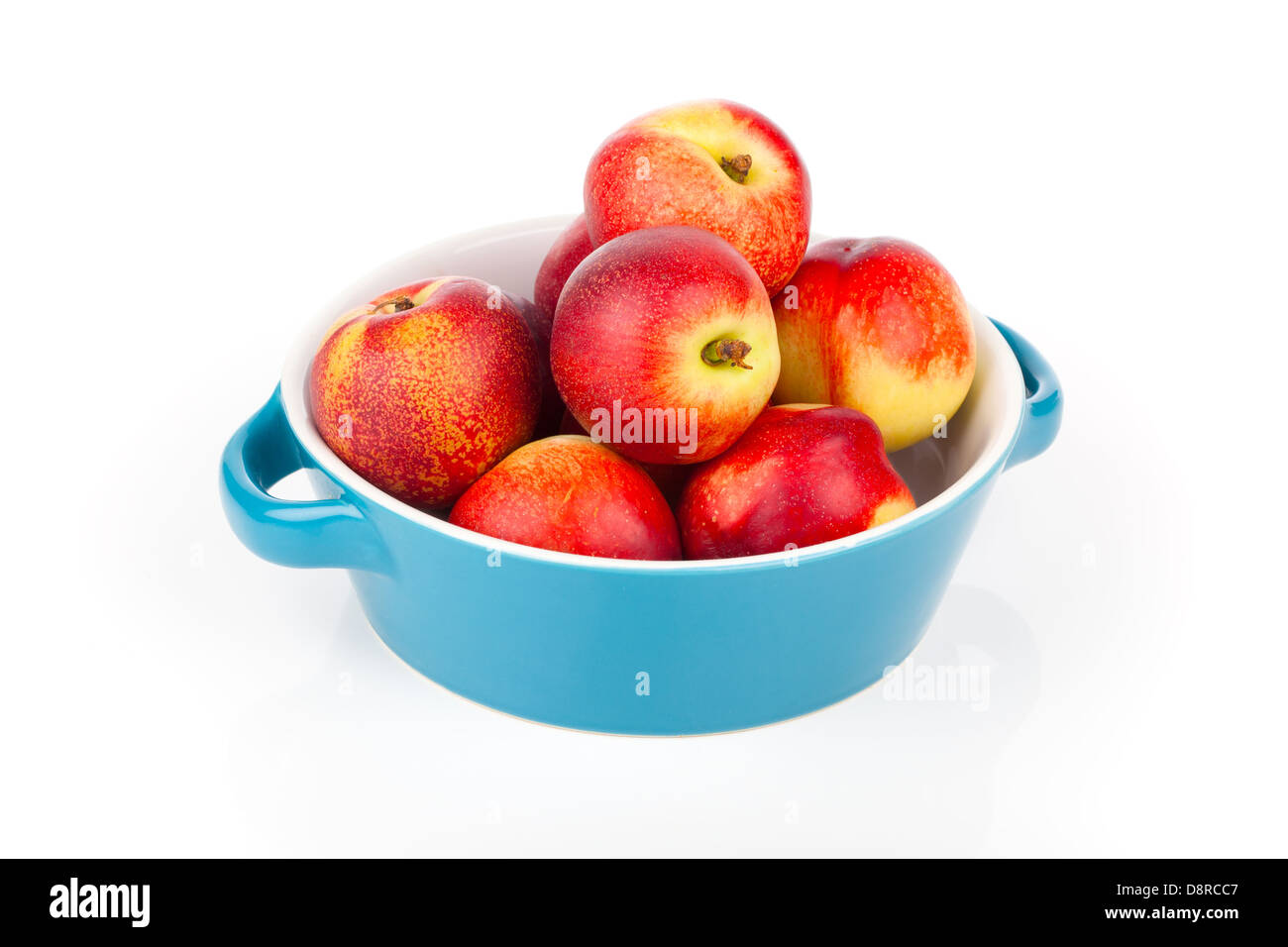 red ripe nectarine peaches on bowl, isolated on white - Stock Image