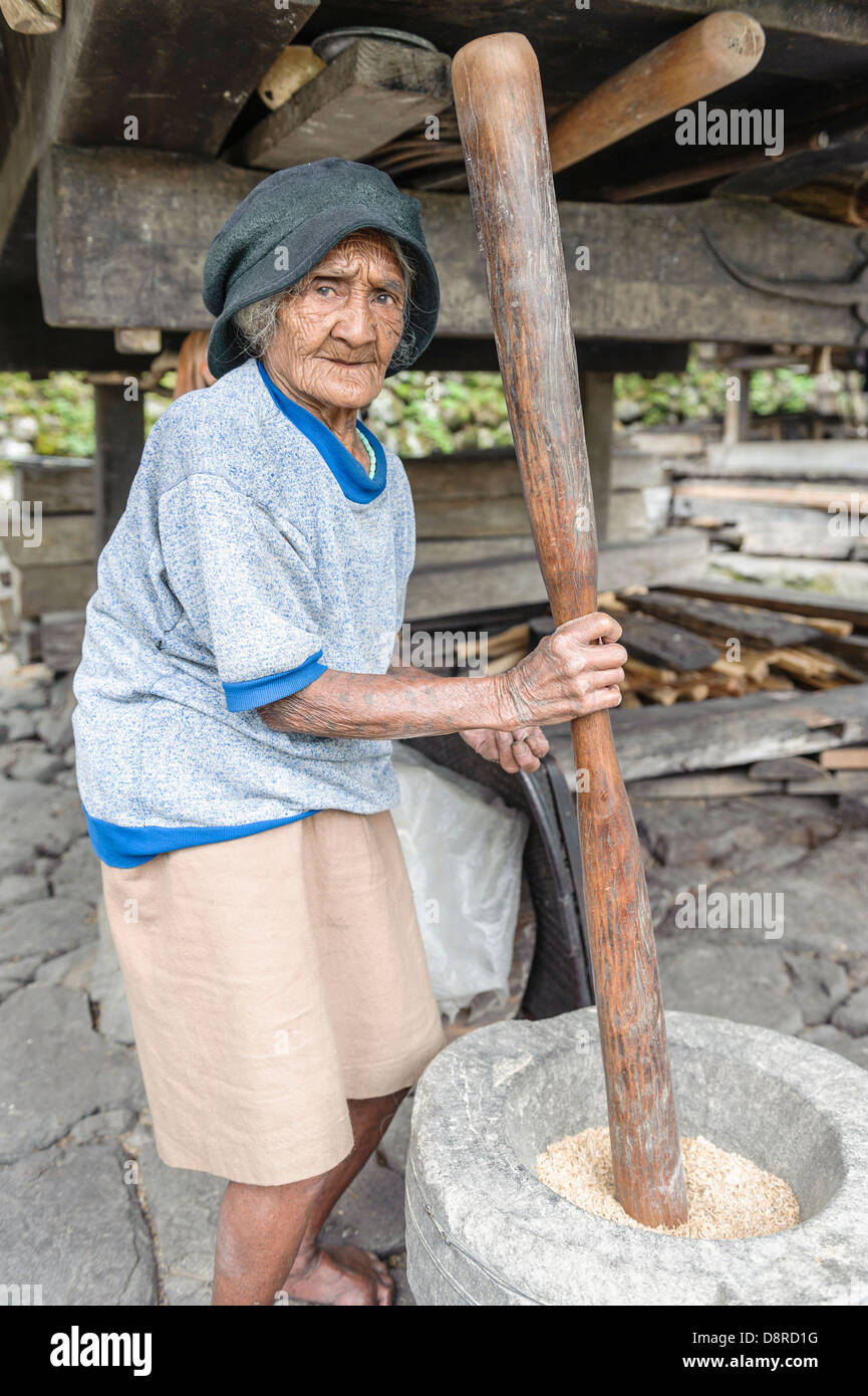 Woman pounding rice in a rural village, Batad, Luzon, Philippines - Stock Image