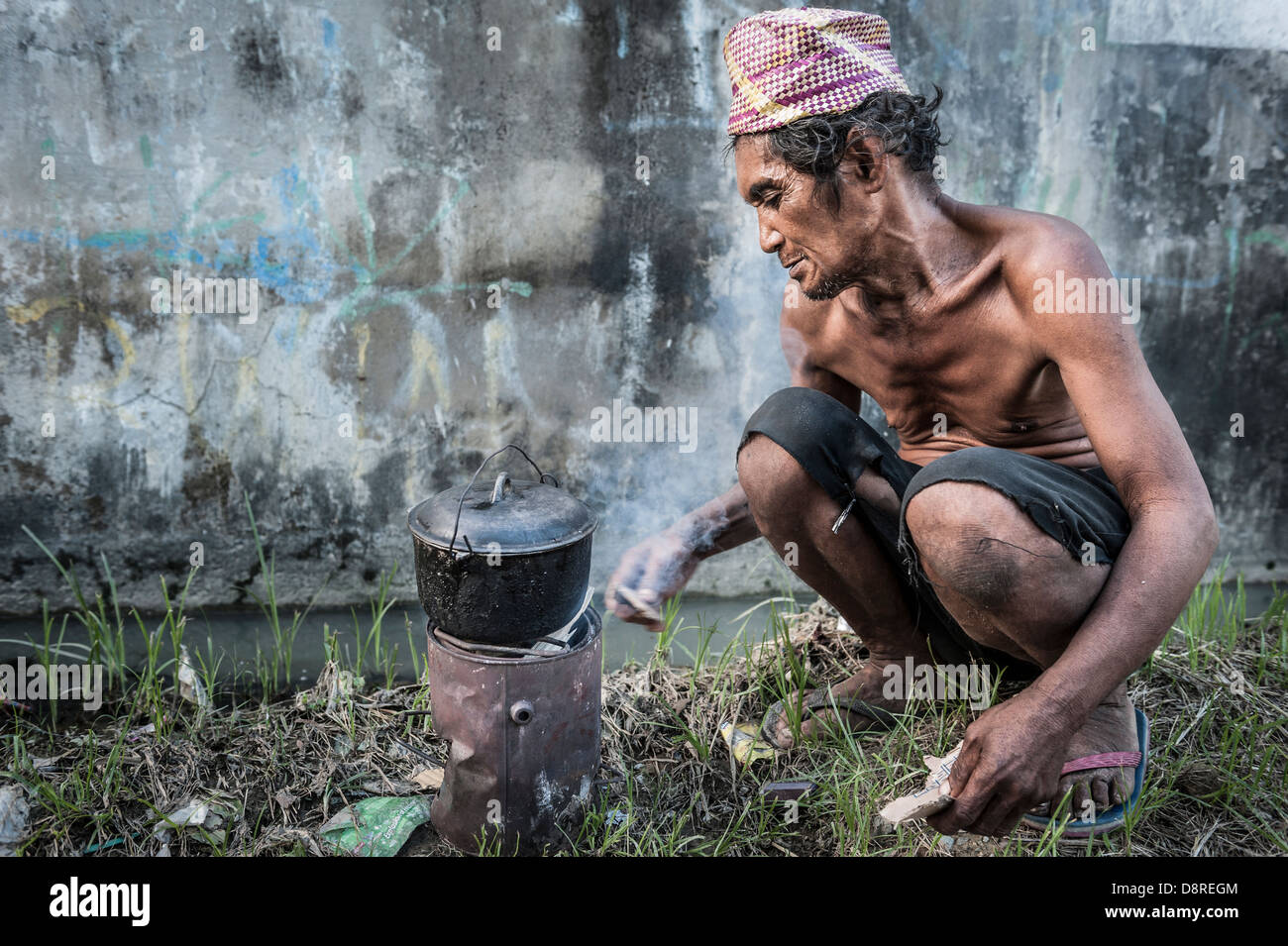 Homeless man cooking in the streets of Cebu, Visayas, Philippines, South East Asia. - Stock Image