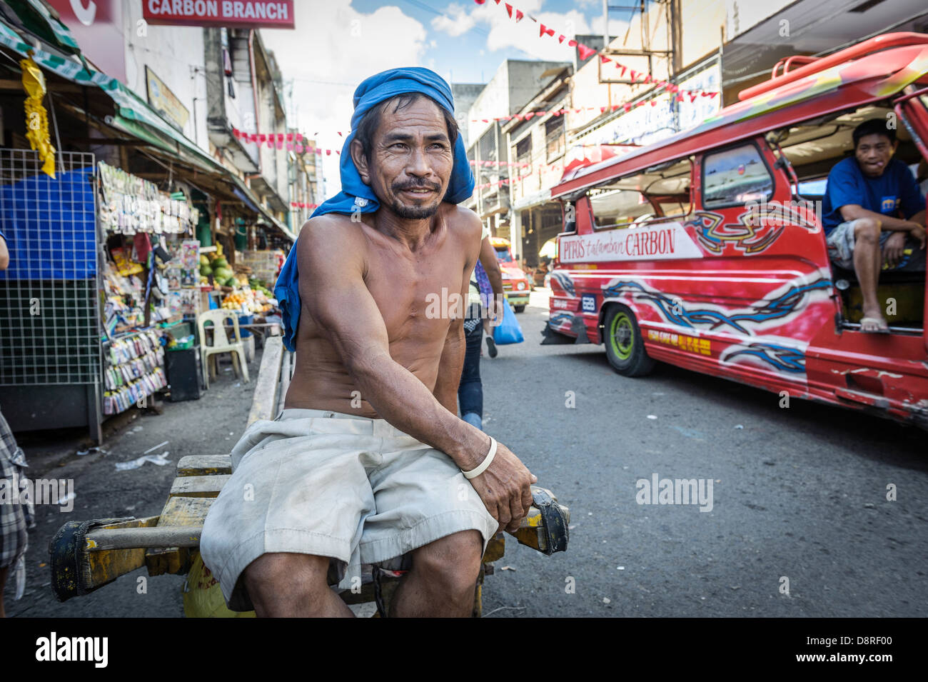 Man sitting on his wheelbarrow waiting for clients, Carbon market, Cebu, Philippines - Stock Image